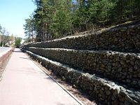 Mur oporowy z gabionów wzdłuż drogi rowerowej w Magdalence
