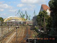 Z wiaduktu nad linia kolejową w ciągu Alei Zwycięstwa widać żurawie portu w Gdańsku